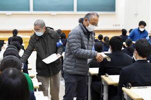 受験生に問題用紙を配るマスク姿の試験官=25日午前9時10分ごろ、佐賀市の佐賀大学本庄キャンパス