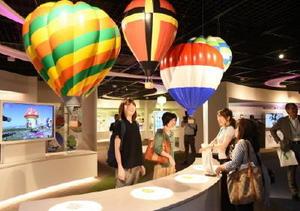 「佐賀バルーンミュージアム」の内覧会で、熱気球に関する展示を楽しむ招待客=佐賀市松原