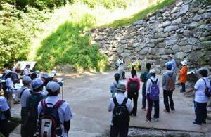 基肄城跡の南端にあたる水門跡で、ボランティアガイドから解説を聞く参加者たち=基山町