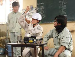 製品検査の方法を体験する塩田工高の生徒(中央)=神埼市の佐賀宇部コンクリート工業佐賀工場