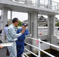佐賀市中心市街地を流れる新村愛敬雨水幹線を視察し、水防対策の現状について説明を受ける秀島市長(右)=佐賀市大財