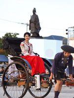 人力車に乗って出発する鍋島栄子役の三根梓さん。奥は鍋島直正公銅像=佐賀市城内