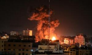 17日、イスラエル軍の空爆後、煙を上げる建物=パレスチナ自治区ガザ(ゲッティ=共同)