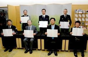 緊急消防援助隊への食料提供に関する協定書を手にする山口祥義知事と県生協連の喜多裕彦会長(前列左から2人目)と県内5消防機関の代表=佐賀県庁