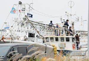 金塊を運んだ小型船を調べる捜査員ら。網を巻き上げる機械は取り付けられていなかった=1日、唐津市鎮西町の名護屋漁港