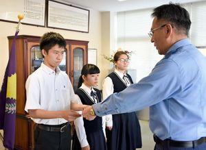 原恭二署長から指定書を受け取る唐津西高の池田光輝さん(左)=唐津警察署