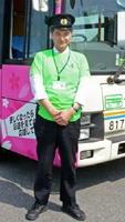 ラッピングバスとTシャツをアピールする市交通局の運転手=県総合運動場