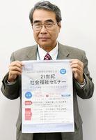 「21世紀社会福祉セミナー」のチラシを持つ、佐賀県社会福祉士会の鶴敏弘さん