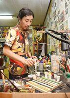 手元の様子をライブ配信しながら、作品を描き上げる冨永ボンドさん=多久市
