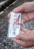 自衛隊ヘリから落下したとみられるお守り。墜落現場から約800メートル離れた江口敏満さん方近くで見つかった=6日午前9時15分ごろ、神埼市千代田町詫田
