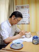 「山水画を学んだことが今の仕事に大いに役立っている」と話す山口博和さん=有田町の自宅