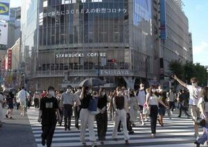 東京・渋谷駅前を歩く人たち。後方の電光掲示板には3千人を超えた東京都の新型コロナ新規感染者数が表示されていた=1日午後