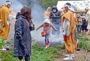 焼けた炭の上をはだしで歩く参拝者=白石町の稲佐山玉泉坊