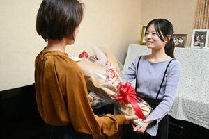 母の蘭文恵さん(手前)に花束を手渡す瑞歩さん=佐賀市