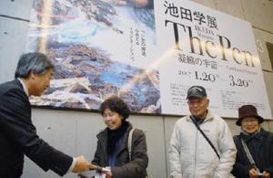 佐賀新聞社の峰松洋史事業部長(左)から、池田さんのサイン入り図録を受け取る山下さん=佐賀市の県立美術館
