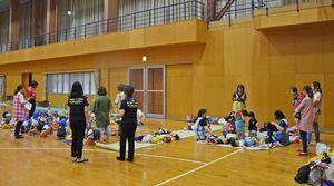大雨の影響でトヨタ紡織九州の体育館に避難した仁比山保育園の園児と職員=6日午後0時55分ごろ、神埼市神埼町