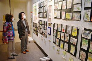 絵手紙作品を鑑賞する佐賀市の秋山恵子さん(左)と花島富士枝さん(右)=佐賀市白山のエスプラッツホール