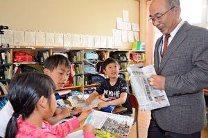 新聞を読み比べながら違いを見つける児童たち=唐津市の佐志小