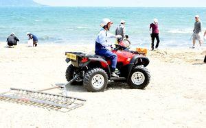 「ビーチクリーナー」(後部)を搭載して砂浜を走行するホンダ製のバギー=唐津市の東の浜海水浴場