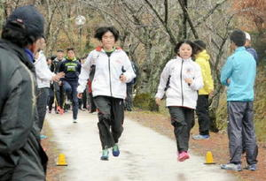 下り坂を片足でジャンプしながらトレーニングする短距離走の選手ら=伊万里市の国見台運動公園