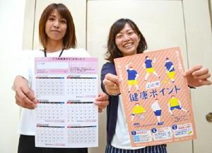 健康ポイントのチラシ(右)とポイントカードを掲げる同町福祉課職員=江北町役場