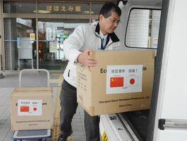 中国の連雲港市に送るマスク1万枚を入れた段ボールを積み込む佐賀市職員=兵庫北のほほえみ館