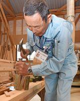 金づちとのみで竹を割る岩本重男さん=小城市芦刈町の匠美建築工房作業場