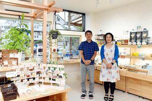 雑貨や焼き物の器が並ぶ「あいう」の店内と横石さん夫婦=武雄市武雄町