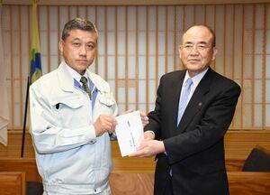 秀島敏行市長に目録を手渡す天山環境開発工業の互助会代表の石井久彦さん(左)=佐賀市役所