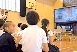 フランスの児童が写真を見せながら語る体験談に、笑みを浮かべる脊振小の児童=神埼市の同校