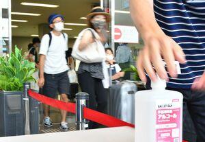 お盆休みを佐賀で過ごす人たちの帰省が8日、本格化した。佐賀空港では、到着直後に手を消毒するなど新型コロナウイルスの感染防止に気を配りつつ、マスク越しの笑顔で再会を喜ぶ人たちの姿も目立った=佐賀市川副町