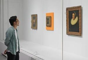 バロック展を訪れ、絵画を見て回る画家の池田学さん=佐賀市の県立美術館