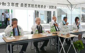 神埼桑菱茶の試飲をする松本茂幸神埼市長(左)ら=神埼市の神埼情報館前