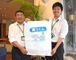 育つくんの袋を手にする大川柳川衛生組合の中川初治事務局長(左)ら=佐賀市の佐賀新聞社