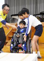 岸田君の乗った車いすで段差を乗り越える練習をする児童=鳥栖市の旭小