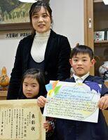 ありがとうの手紙コンテスト2019で最優秀賞に選ばれた石本航雅君(右)と受賞を祝う母美保さん、妹莉野ちゃん=鹿島市の鹿島小