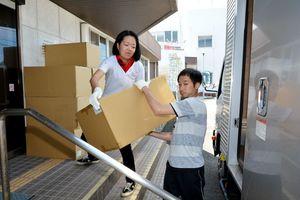 下着などの支援物資をトラックに積み込むA-PADジャパンの職員(左)とボランティア=佐賀市久保田支所