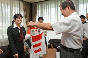 女子ラグビーワールドカップの試合で実際に着ていたユニホームを嬉野市の谷口太一郎市長(右)に贈る堤ほの花選手=嬉野市役所嬉野庁舎
