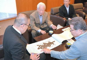 江里口市長にカレンダーに掲載した梧竹の書について説明する山口三郎氏(右)=小城市役所