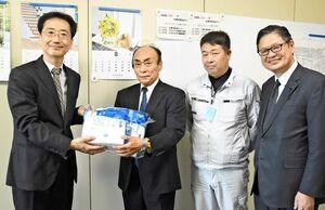 大川内直人健康福祉部長(左)にタイベックスーツやマスクを手渡した渡島秀昭代表取締役(左から2人目)=佐賀県庁