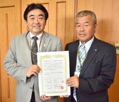 見守りネットワークに関する協定を結んだ、県医薬品配置協議会の大山泰人会長(右)と松田一也基山町長=基山町役場