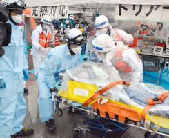 愛知県北名古屋市の総合防災訓練で、新型コロナウイルス感染の疑いを想定し搬送される特養の入所者役=13日