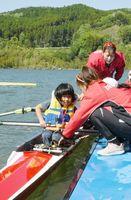 選手に支えてもらいながら、緊張した面持ちでボートに乗りこむ参加者=富士しゃくなげ湖