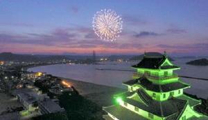 上空から宵闇に浮かび上がる唐津城、西の浜、花火の3点セットを俯瞰(ふかん)する=小型無人機「ドローン」から