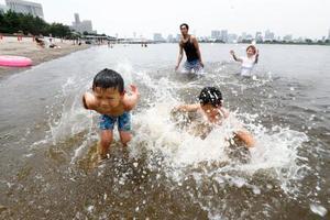 猛暑が続く東京・お台場海浜公園で水遊びする家族連れ=22日午前