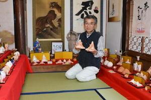 赤土を使った新作土びな人形を手にする聖心房主の倉富博美さん=多久市多久町