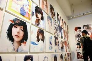 無表情な女子高生の視線が見る人に注がれ、独特の世界観を醸し出す個展会場=福岡市中央区のタグスタ