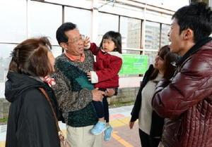 年末年始を佐賀で過ごし、広島に帰る家族。女の子は祖父に抱っこされ、別れを惜しんでいた=佐賀市のJR佐賀駅