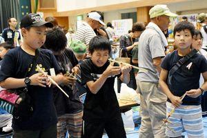 竹で作った鉄砲で射的を楽しむ子どもたち