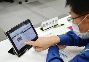 G空間情報収集システムでタブレットを操作し、災害現場の情報を確認する市職員